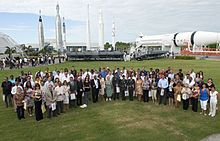People are seen standing in a field at the Kennedy Space Center during a naturalization ceremony.