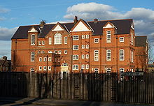 A large red and yellow brick school of a similar Gothic design to the previous photographs of houses but on a much larger scale