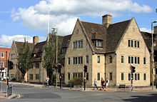 Adjoining buildings at the corner of a road, facing both ways; a mixture of gables and dormer windows at the roofline; built of light-coloured stone, they are two-storey in height below the roofs or gables