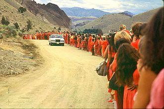 """Rajneeshpuram - Rajneesh greeted by followers on one of his daily """"drive-bys"""" in Rajneeshpuram. Circa 1982."""
