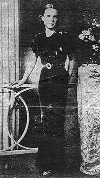 A black and white photograph of a young woman wearing a floor-length black dress with short sleeves, her right hand on a neighboring table and her left hand behind her as she faces the camera. In the middle of the image a paper crease is visible.