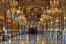 Foto av et glitrende galleri under to rader med lysestaker, på hver side av søylene og på baksiden av et alter