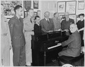 Photograph of President Truman in the Fish Room of the White House, playing a piano given to him by the Piano... - NARA - 200297.tif