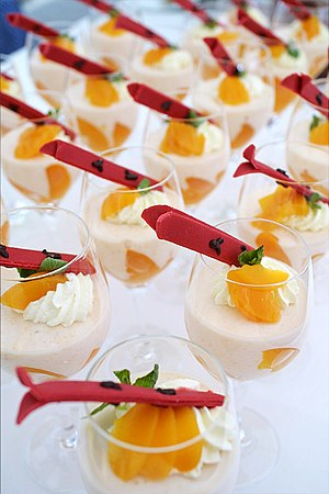 Garnish (food) - Peach mousse garnished with whipped cream, mint leaves, additional peaches and ski-shaped confectionery