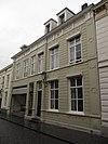 foto van Huis met gebosseerd grijsgepleisterde lijstgevel uit plm 1850, zadeldak