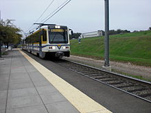A white and yellow light rail train approaches an empty station platform with overhead lines visible above.