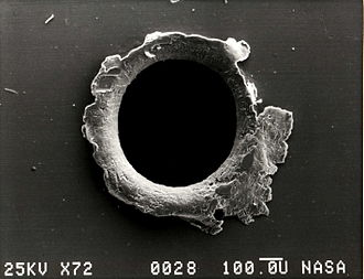 Micrometeoroid - Electron micrograph image of an orbital debris hole made in the panel of the Solar Max satellite.