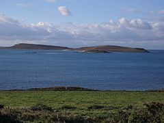 Looking from the grassy shore of Tresco, across the calm water, to the low twin hills of Samson