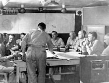 Nine men sit around a large table. Another is standing, leaning over the table. On the wall behind them are maps of the Pacific Ocean and Enewetak Atoll.