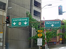"A set of green highway signs reading ""Southbound US 99"" and ""Waterfront"" seen above a street intersection."