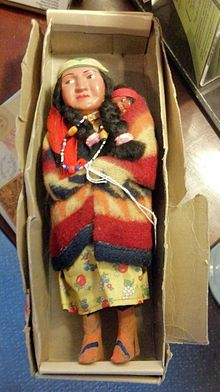 A female Indian doll wrapped in a blanket with a baby, in an old cardboard box