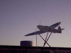 Spitfire replica, with auto-manufacturer logo in background