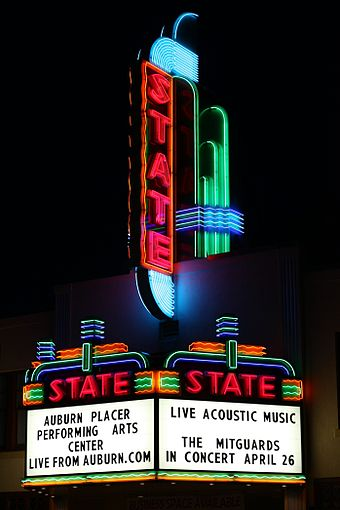 "1936 neon marquee sign for a theater in Auburn, California, as rebuilt in 2006. The large letters on the tower are illuminated in a timed sequence that repeats, ""S"", ""ST"", ""STA"", ""STAT"", ""STATE"", off."