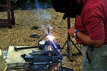 English: A guy stick welding.