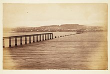 Sepia photograph of the Tay Bridge after the accident. Shot from the South it shows the middle section of the bridge to be missing.