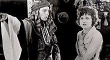 Black and white screenshot from the film The Sheik, with the man in Arab costume and the woman in Western clothing.