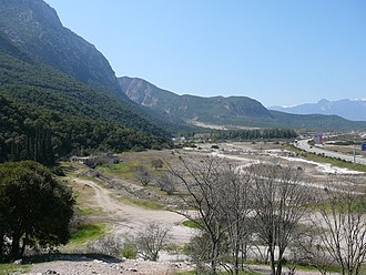 Battle of Thermopylae - The site of the battle today. Mount Kallidromon on the left, and the wide coastal plain formed by accretion of fluvial deposits over the centuries; the road to the right approximates the 480 BC shoreline.