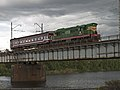 Train on a railway bridge over Maza Daugava.jpg