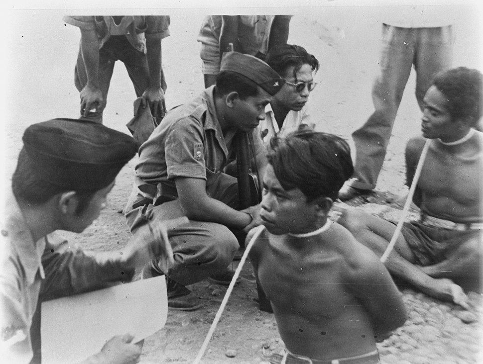 Twee mannen met touw geboeid worden ondervraagd door TNI-officieren, Bestanddeelnr 8812