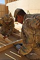 U.S. Army Spc. Jason Donelson, left, and Spc. Jared Jordan, both with the 149th Vertical Construction Company, Kentucky Army National Guard, build a frame for a wall in a tactical operations center at Forward 130820-A-NQ567-135.jpg