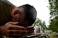 U.S. Army Spc. Jesse Rameriz, with Headquarters and Headquarters Company, 105th Military Police Battalion, North Carolina Army National Guard, rinses himself with water after being exposed to oleoresin capsicum 130501-Z-AY498-013.jpg
