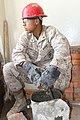 U.S. Marine Corps Lance Cpl. Jaicinio Jarrettsoto, with the 9th Engineer Support Battalion, 3rd Marine Logistics Group, III Marine Expeditionary Force, takes a break from making mortar for laying bricks during 130727-M-DR618-076.jpg