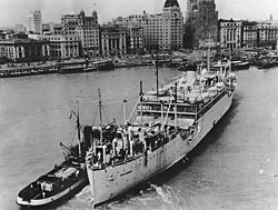 The USS Chaumont, a large light-coloured transport vessel with a smaller vessel alongside, against a background of shorefront buildings and docked ships