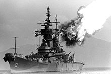 A black and white image; a large ship with gun barrels pointed to the right and up, flames and smoke can be seen emanating from the gun barrels.