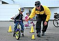 US Navy 030804-N-9005E-001 Aircrew Survival Equipmentman Airman Jeff Martin, a Naval Station bike patrolman, guides a 5 years old through an obstacle course.jpg