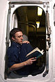 US Navy 040630-N-8774S-005 Interior Communications Electrician 3rd Class Matthew M. Zubrzycki enjoys a book while waiting for a coat of wax to dry, during routine ships upkeep aboard USS Harry S. Truman (CVN 75).jpg