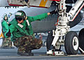 US Navy 051020-N-0119G-009 Aviation Boatswain's Mate 2nd Class Brandon Donelow guides an F-A-18C Hornet onto a catapult.jpg