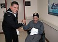 US Navy 051202-N-4936C-002 U.S. Navy Damage Controlman 1st Class Henry Guevara embraces a resident of the Philadelphia Veterans Affairs Medical Center Nursing Home.jpg