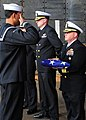 US Navy 091212-N-7298E-021 Seaman Apprentice Josue Fernandez-Lopez salutes Cmdr. Fred R. Wilhelm after handing him the American flag during a burial at sea.jpg