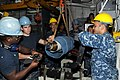 US Navy 111129-N-JB593-034 Sailors assigned to the submarine tender USS Frank Cable (AS 40) hoist a trim pump rotor onto the rotor balancing machin.jpg
