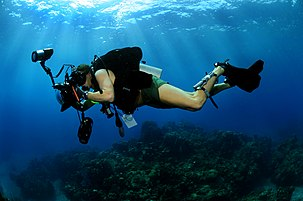 A scuba diver swims over a reef with a large still camera in an underwater housing with dome port and electronic strobes.