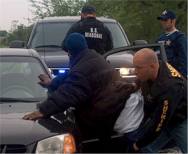 Datei:United States Marshal searching a fugitive.jpg