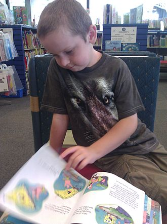Long Beach Public Library - A child reading a book inside the Main library.