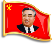 Red, flag-shaped pin with a smiling Kim Il-sung