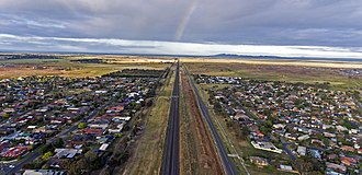 Werribee, Victoria - Werribee's western periphery seen from the sky with a sliver of rainbow right over the freight train line in the middle of the shot: Aerial panorama shot in November 2017. Facing west and the You Yangs.