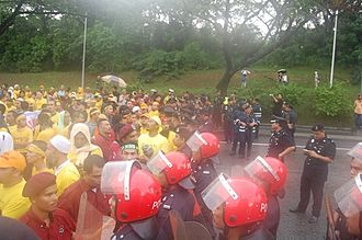 Bersih 2.0 rally - A scene from the 2007 rally. Protestors on the left are dressed in yellow. They are met by the Federal Reserve Unit, the riot police (in red helmets). Standing in between the protestors and the riot police are PAS's Jabatan Amal volunteer unit (dressed in maroon).