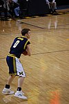 A basketball player in a dark blue uniform has the ball in his hands in the open court.