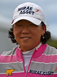 A brunette in a white hat with black lettering and gray and pink striped shirt