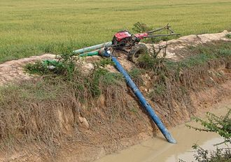 Axial-flow pump - Thai model 8 inch x 20 foot long axial flow pump powered by 12 horsepower two-wheel tractor lifting water from an irrigation canal into nearby rice fields via plastic flexible delivery pipe