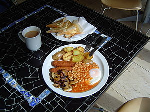 Two veggie sausages, baked beans, fried mushrooms, fried eggs, fried potatoes, toast and tea