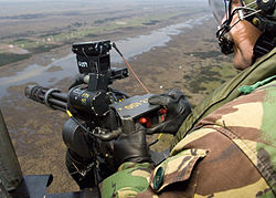 A door gunner mans a M134 six barrelled 7.62mm Minigun onboard a Royal Air Force Chinook MOD 45147887.jpg