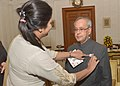 A member of the Indian Red Cross Society (National Capital Territory Branch), Delhi, pinning a flag to the President, Shri Pranab Mukherjee, on the occasion of the Red Cross Flag Week, at Rashtrapati Bhavan, in New Delhi.jpg