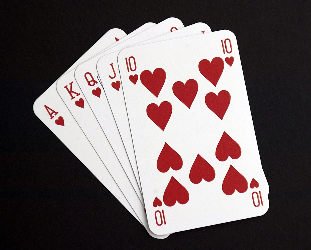 Five playing cards– the ace, king, queen, jack and ten of hearts– spread out in a fan.