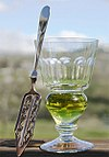 A reservoir glass filled with a naturally colored verte next to an absinthe spoon.