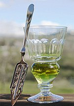 A reservoir glass filled with absinthe next to an absinthe spoon.