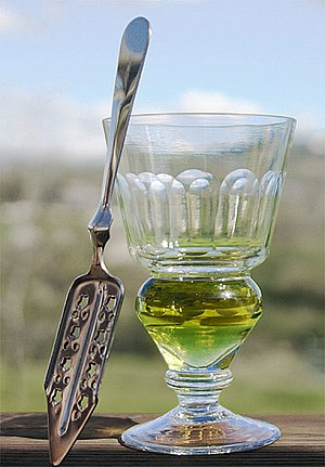 Absinthe - Reservoir glass with naturally coloured verte absinthe and an absinthe spoon